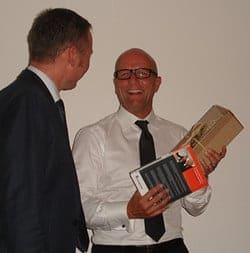Thomas Issler übergibt Andreas Buhr einen Stuttgarter Wein und sein Buch Der Internet-Marketing-Plan für Handwerksunternehmen